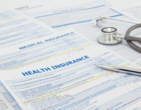 Medical insurance application, silver pen and stethoscope. Legal law contract and health insurance concepts.